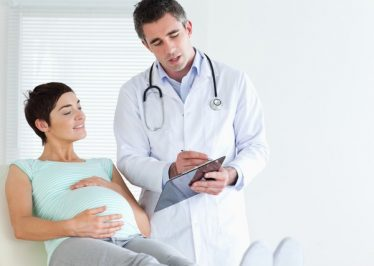Pregnant woman lying down talking to her doctor